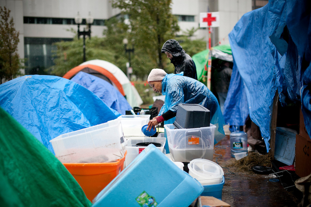 Occupy Boston members wash dishes as a part of their daily life at Dewey Square in Bosrton, Massachusetts, October 29, 2011.