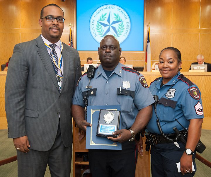 Houston ISD Employee of the Month Officer Vincent Jones, center, poses with Holland Middle School principal Tarrynce Robinson, left, and HISD Police Sergeant Sabrina Naulings, right, after being recognized during a Board of Education meeting, May 9, 2013.