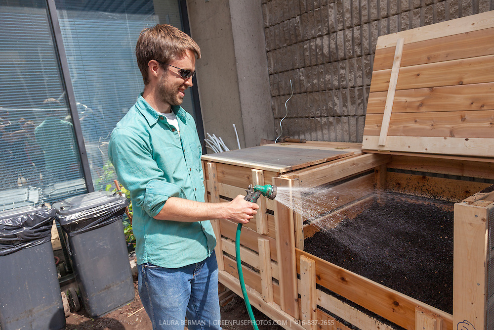 A young man uses a hose sprayer to wet compost down in a wooden compost bin.