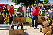 "06 AUGUST 2020 - FAIRFIELD, IOWA: Bid spotters TERRY HOENIG, right, and ED SHOVER, left, with a pallet of stuff being auctioned on the Adam Farm near Fairfield. Gary Adam, 72 years old, has been farming in the Fairfield area since 1971. He decided to retire this year because he wants to travel and because it's so difficult to make money in farming this year. He said he wants to ""shed the risk and responsibility. If things were super good, like they were 2006-2012, I might stay in it, but they're not."" An increasing number of farmers in the Midwest are retiring this year as it becomes harder to make money on crops. In addition to low prices, Iowa farmers are being hit with a drought this year, with well below average rain over most of the state. Because of the COVID-19 pandemic, the auction on Adam's farm was one of the first live in person auctions since winter. Most auctions are now done on line.    PHOTO BY JACK KURTZ"