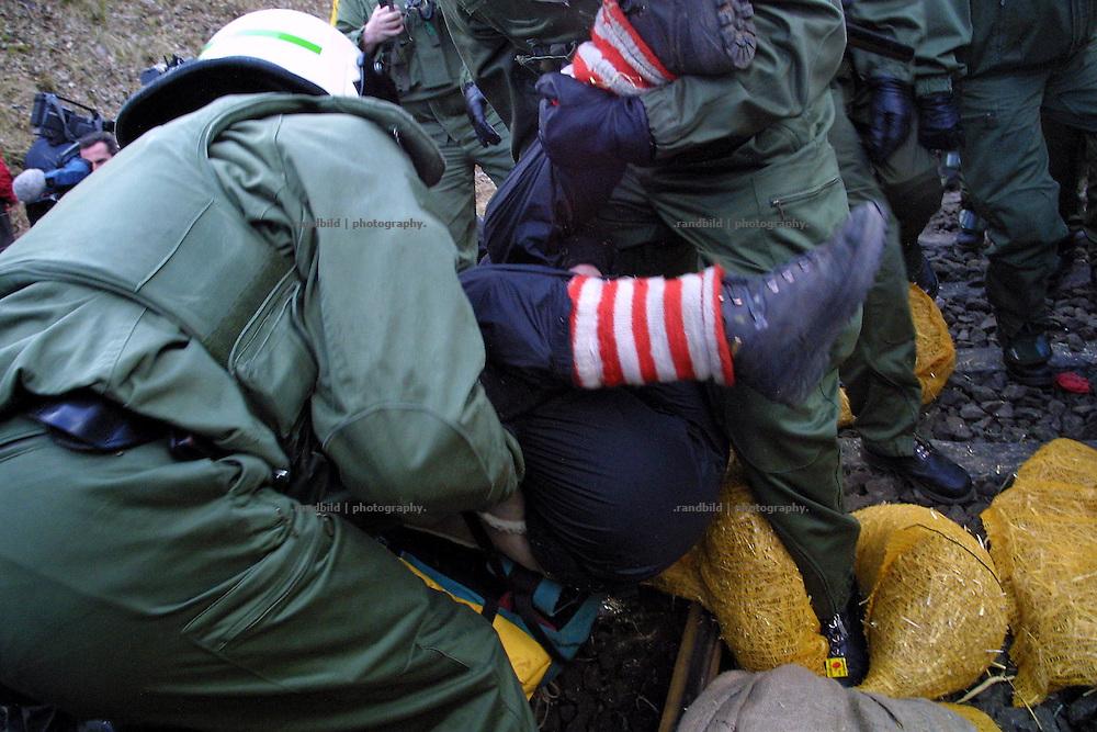 Polizisten tragen eine Demonstrantin von den Gleisen. Sie hatte mit anderen mit einer Sitzblockade einen Castortransport blockieren wollen.