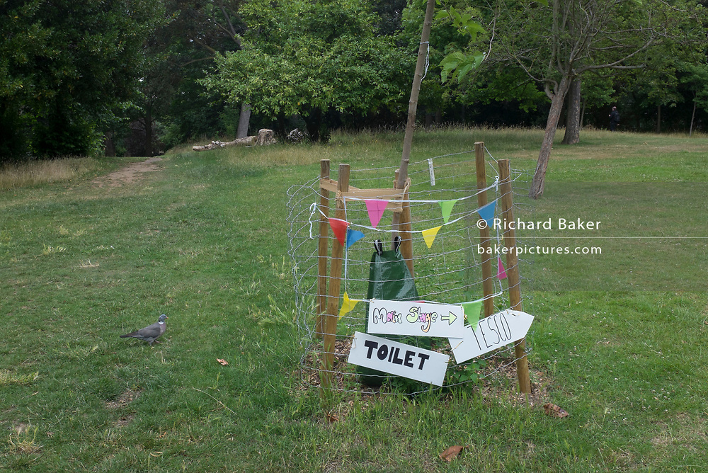 While park conveniences are still closed, makeshift signs pointing to where nearby toilets are located during the Coronavirus pandemic lockdownare, are attatched to the protective fence around a yourg tree in Ruskin Park, Lambeth, on 30th June 2020, in London, England.