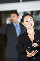 Businesswoman holding folder in front of  businessman using phone
