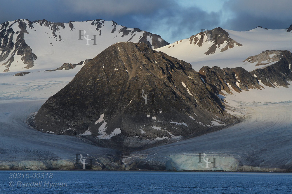 Glaciers flow from mountains to sea in Smeerenburgfjorden on the north coast of Spitsbergen island; Svalbard, Norway.