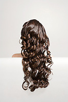 Woman with long brown curly hair rear view
