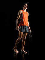 Athlete standing holding shoes low angle view