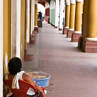 A woman sits by Granada's main square, selling food to passer bys. Granada is Nicaragua's most famous city. founded in 1524 it is one of best examples of Spanish colonial architecture in the Americas. .it has a varied history including its almost total destruction by filibuster William Walker in a childlike tantrum. Today it is a popular tourist town though retains a strong sense of its own identity.