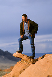 Man looking at the view from top of a rock formation in Nevada