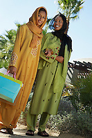 Two muslim women in traditional clothing, one with shopping bag