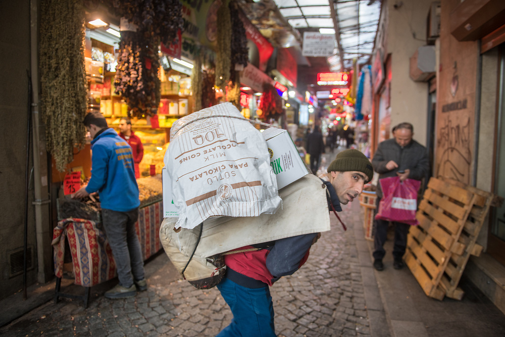 An adult male carries several heavy bags of goods on his back at outdoor marketplace, Istanbul, Turkey
