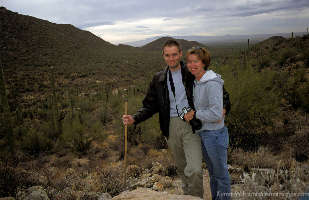 North America, USA; Arizona. Hikers in the Saguaro National Park pause to capture a scenic moment on the trail.
