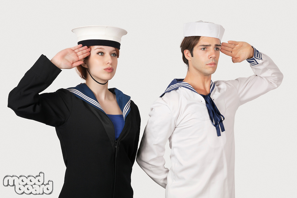 Young man and woman in sailor's uniform saluting against gray background