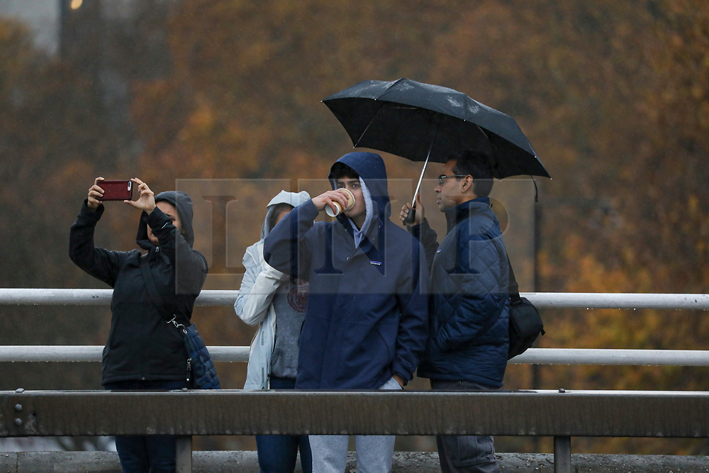 © Licensed to London News Pictures. 26/11/2019. London, UK. Commuters and tourist walk over Waterloo Bridge in the rain while Storm Sebastien continues to batter the South of England as the Met Office issue weather warnings for the South West.