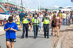 © Licensed to London News Pictures. 01/08/2020. Brighton, UK. Police officers patrol the seafront as thousands of people take to the beach in Brighton and Hove as sunny weather hits the seaside resort. Photo credit: Hugo Michiels/LNP