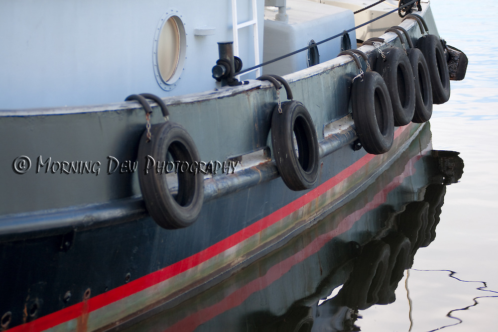 "Tires hang from the side of the tug boat ""Raven"" as it is moored at the Tarpon Sponge Docks."