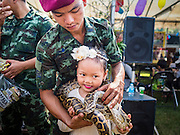 "14 JANUARY 2017 - BANGKOK, THAILAND: A Thai soldier puts a python around a child's neck during Children's Day activities at the King's Guard, 2nd Cavalry Division base in Bangkok. Thailand National Children's Day is celebrated on the second Saturday in January. Known as ""Wan Dek"" in Thailand, Children's Day is celebrated to give children the opportunity to have fun and to create awareness about their significant role towards the development of the country. Many government offices open to tours and military bases hold special children's day events. It was established as a holiday in 1955.        PHOTO BY JACK KURTZ"