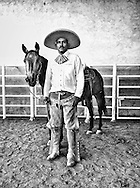 A Charro poses in front of his horse
