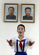 A North Korean student sings a song under portraits of North Korea's late leader Kim Il-sung (L) and leader Kim Jong-il at a class room of the Mankyongdae juvenile student palace in Pyongyang. Photo by Lee Jae-Won (NORTH KOREA) www.leejaewonpix.com/