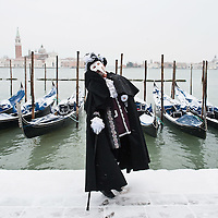VENICE, ITALY - FEBRUARY 12:  A man wearing a Canival costume poses for pictures in the snow in St Mark's Square on February 12, 2012 in Venice, Italy. Italy, like most of Europe, is experiencing freezing temperatures, with the Venice Lagoon freeezing for the first time in over 20 years.