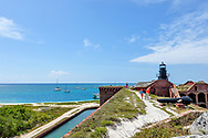Kids explore the fortifications on the rooftop of Fort Jefferson at Dry Tortugas National Park. They walk along a path on the roof with view of lighthouse, water and sailboats. Model released photo.