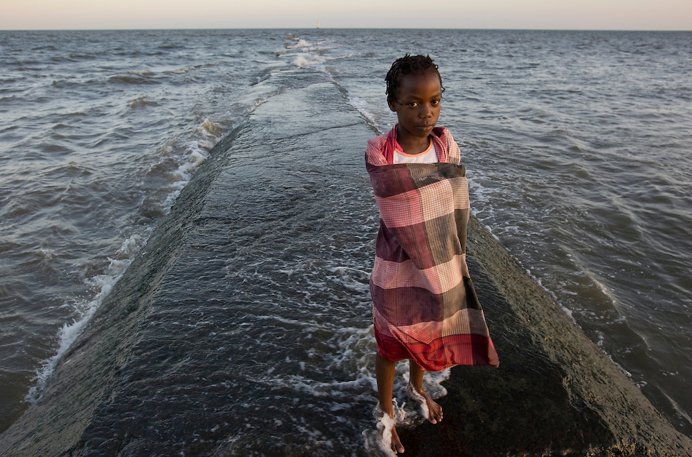 Africa, Mozambique, Maputo, Portrait of young girl standing on jetty wrapped in towel along Indian Ocean at sunset