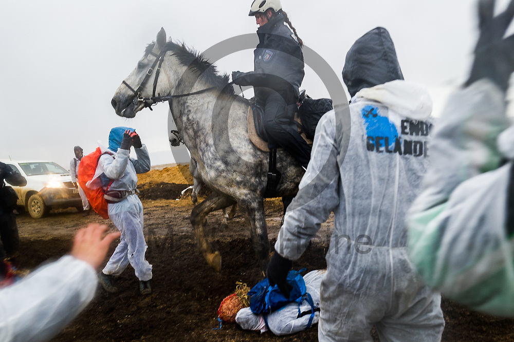 Deutschland, Elsdorf - 05.11.2017<br /> <br /> Ein Pferd der berittenen Polizei tritt auf eine Aktivistin. Circa 2500 Aktivisten drangen in die Grube des Braunkohle Tagebau Hambach ein um mit der Aktion f&uuml;r einen sofortigen Kohleausstieg zu protestieren. Die Aktion fand im Rahmen von Protesten im Vorfeld der UN-Klimakonferenz in Bonn statt.<br /> <br /> Germany, Elsdorf - 05.11.2017<br /> <br /> A horse of the mounted police steps on an activist. Approximately 2500 activists invaded the pit of the lignite opencast mine Hambach to protest for an immediate coal exit. The action took place during protests prior to to the UN Climate Change Conference in Bonn.<br /> <br />  Foto: Markus Heine<br /> <br /> ------------------------------<br /> <br /> Ver&ouml;ffentlichung nur mit Fotografennennung, sowie gegen Honorar und Belegexemplar.<br /> <br /> Bankverbindung:<br /> IBAN: DE65660908000004437497<br /> BIC CODE: GENODE61BBB<br /> Badische Beamten Bank Karlsruhe<br /> <br /> USt-IdNr: DE291853306<br /> <br /> Please note:<br /> All rights reserved! Don't publish without copyright!<br /> <br /> Stand: 11.2017<br /> <br /> ------------------------------