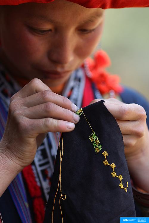Phan Lo May, 24, of the Red Dzao ethnic minority group, sewing near her village in the Highlands of Northern Vietnam close to the Chinese border. Northern Vietnam is inhabited by highland minorities including Hmong and Dzao groups who trade with tourists in Sapa. Sapa is now a thriving tourist destination for travelers taking the night train from Hanoi. Sapa, Vietnam. 16th March 2012. Photo Tim Clayton