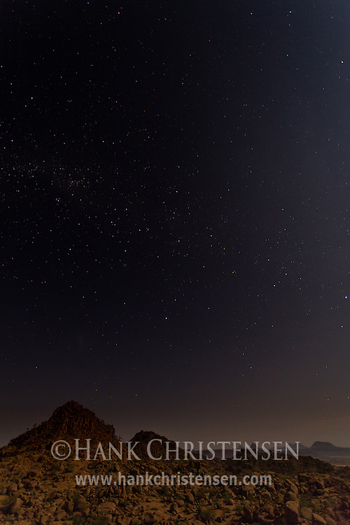 Stars light the night sky over the desert landscape of Damaraland, Twyfelfontein, Namibia.