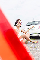 Frustrated woman using cell phone while sitting by broken down car