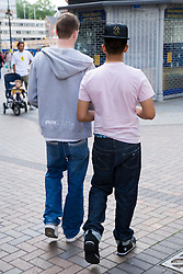 Two teenaged boys walking down the street together,