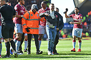 A pitch invader is led from the pitch followingg his assault on Aston Villa midfielder Jack Grealish (10) during the EFL Sky Bet Championship match between Birmingham City and Aston Villa at St Andrews, Birmingham, England on 10 March 2019.