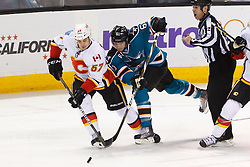 Feb 8, 2012; San Jose, CA, USA; Calgary Flames center Lance Bouma (57) and San Jose Sharks defenseman Justin Braun (61) fight for a loose puck during the first period at HP Pavilion. Mandatory Credit: Jason O. Watson-US PRESSWIRE