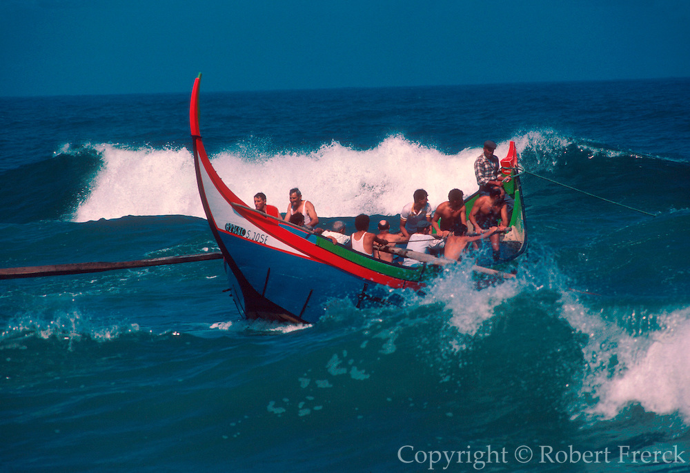 PORTUGAL, CENTRAL, ATLANTIC COAST fishermen rowing traditional wooden boats in sea off of Mira south of Aveiro