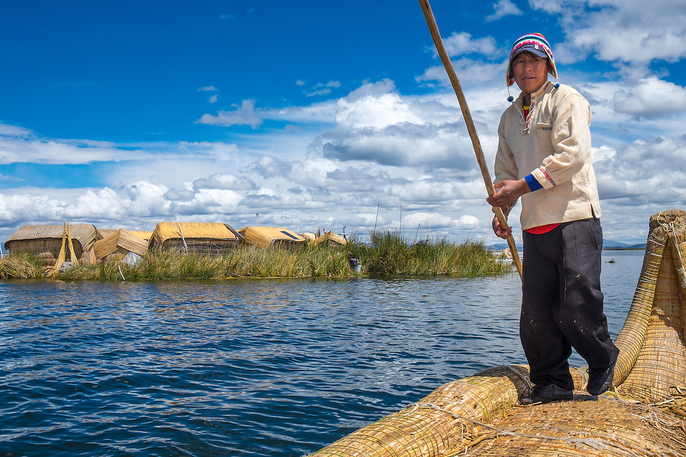 UROS ISLANDS, PERU - CIRCA APRIL 2014: Man from the Uros Islands in Lake Titicaca rowing in typical canoe made of totora reeds.