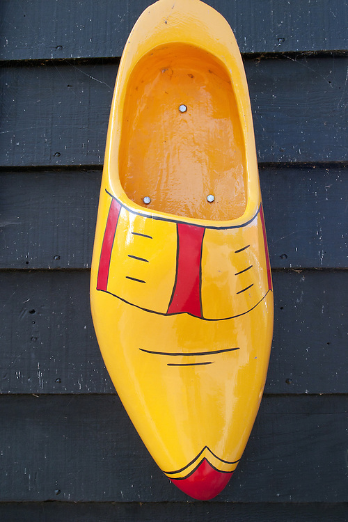 """A brightly colored wooden shoe marks the shoemaker's shop within the Zaanse Schans historical area. This historic village, known for its antique wooden windmills,  is a popular day trip for Amsterdam visitors.  .From Wikipedia: """" Zaanse Schans is a neighbourhood of Zaandam, near Zaandijk in the municipality of Zaanstad in the Netherlands, in the province of North Holland. It has a collection of well-preserved historic windmills and houses; the ca. 35 houses from all over the Zaanstreek were moved to the museum area in the 1970s. The Zaans Museum, established in 1994, is located in the Zaanse Schans..The Zaanse Schans is one of the popular tourist attractions of the region and an anchor point of ERIH, the European Route of Industrial Heritage. The neighbourhood attracts approximately 900,000 visitors every year..The windmills were built after 1574."""".Also from Wikipedia: """" Along the river Zaan, you can find still dozens of original windmills (mostly entirely made of wood), still technically functioning, some of them over 350 years old. Next to these there are many 19th century stone industrial buildings, nowadays derelict or converted into apartments, but still recognisable as industrial buildings.""""."""