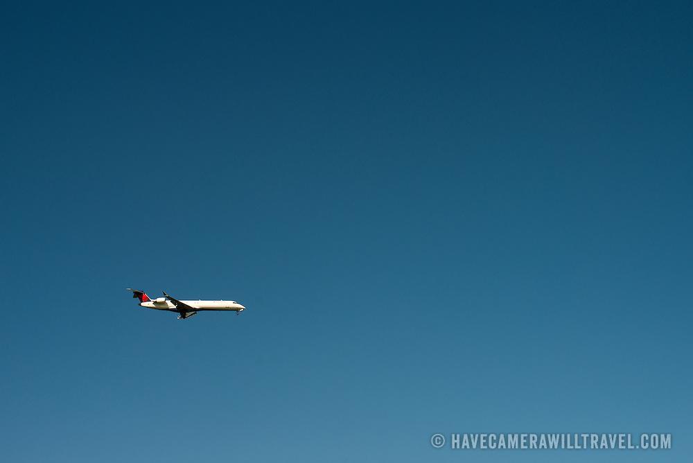 A Delta Connect passenger jet against a clear blue sky.
