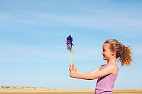 Girl standing on windy beach holding pinwheel side view