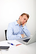 Tired businessman with laptop on desk in office