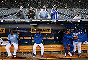 Kansas City Royals catcher Salvador Perez (13) and other teammates sit in the dugout as a rain delay turns into a baseball game called because of snow, at Kauffman Stadium in Kansas City, Mo., Thursday, May 2, 2013.  The Royals were playing the Tampa Bay Rays when the game was stopped in the fourth inning. (AP Photo/Colin E. Braley).