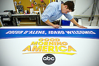 "JEROME A. POLLOS/Press..Scott Meredith trims a vinyl sign Tuesday at Digital Color Print Center in Coeur d'Alene in preparation for the ""Good Morning America"" show."