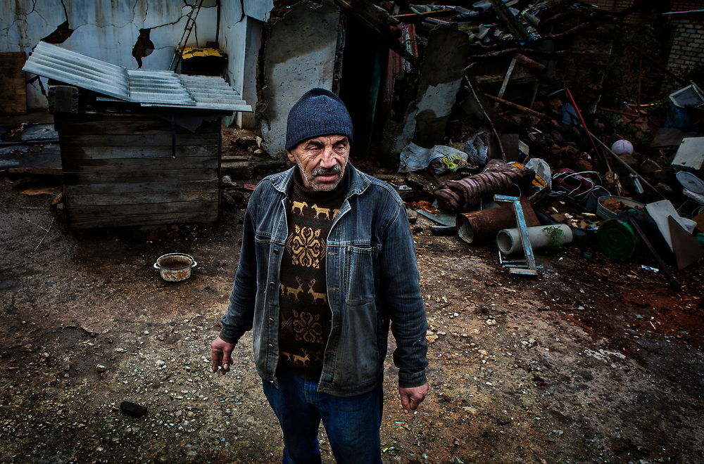 Avdiivka, eastern Ukraine, Nov. 2017.<br /> <br /> Sergey Viktorovych Bocharov, 57, in front of what is left of his garage, after an artillery shell hit it on 23/5/17 that was fired from pro-Russian separatists positions.<br /> <br /> Another one landed in his garden, consequently both shells also caused considerable damage to his house. Fortunately, he and his wife were out at the time.<br /> <br /> He has been building his house for 17 years and refuses to leave it for a safer area - <br /> 'you make it all with your hands, we have lived here all our lives where would we go'.<br /> <br /> He tries to provide support to the few in the area that have also stayed in their homes since the start of the war.  <br /> <br /> One of his close friends who also remained was killed due to the conflict.