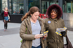 London, UK. 13th February, 2019. A Public & Commercial Services (PCS) union member hands out leaflets on a picket line with outsourced worker colleagues who walked out from the Department of Business, Energy and Industrial Strategy (BEIS) for their second day of strike action to demand the London Living Wage and an end to outsourcing. Union members handed out strike-themed cakes to supporters in return for donations to the strike fund.