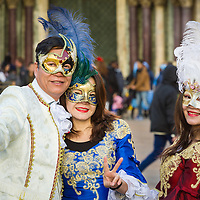 man and woman with young lady wearing colombina masks during Venice Carnival