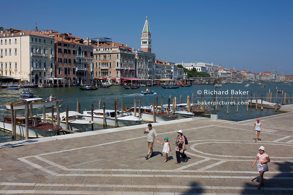 Tourists walk along the waterfront in front of Santa Maria della Salute church in Dorsoduro, overlooking the Grand Canal and San Marco district with the tall Campanile.