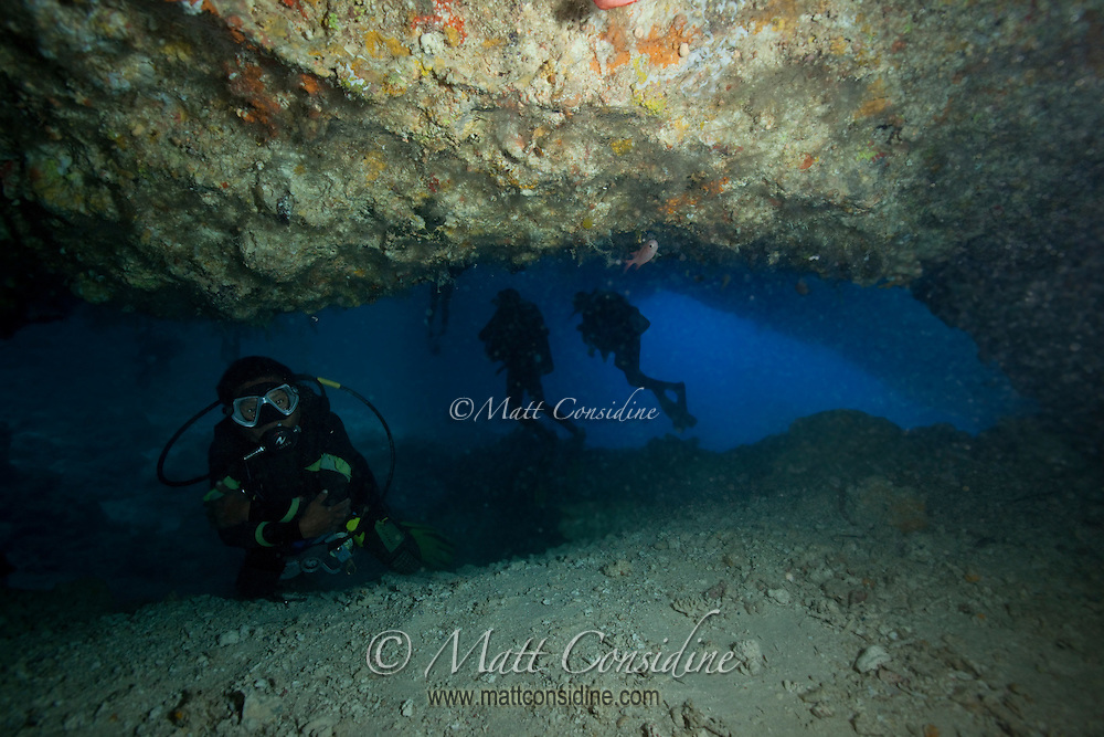 Leaving the aptly named Temple of Doom, with divers in Blue Holes.  Even a few feet from the entrance and exit, there is no light or means of orientation. Even with plenty of artificial light and air, it is easy to see why divers have died here, Palau Micronesia. (Photo by Matt Considine - Images of Asia Collection)