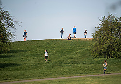 © Licensed to London News Pictures. 12/04/2020. London, UK. People relax on Primrose Hill in London on Easter Sunday, during a pandemic outbreak of the Coronavirus COVID-19 disease. The public have been told they can only leave their homes when absolutely essential, in an attempt to fight the spread of coronavirus COVID-19 disease. Photo credit: Ben Cawthra/LNP