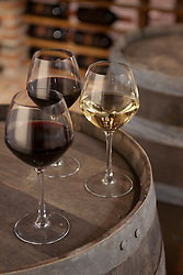 Two glasses of red wine and one glass of white wine on casket barrel in wine celler