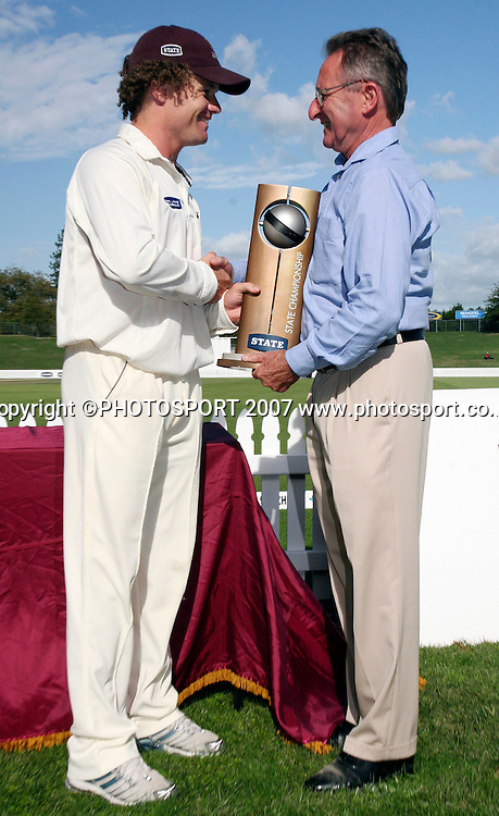 Northern District's captain James Marshall (L) is presented with the State Championship trophy by NZ Cricket President Don Neely (R) after winning the State Championship Cricket Final between Northern Districts and Canterbury at Seddon Park, Hamilton, New Zealand on Monday 26 March 2007. The two teams agreed to a draw - Northern Dirstricts won as Canterbury needed to win outright to take the title. Photo: Hagen Hopkins/PHOTOSPORT<br />