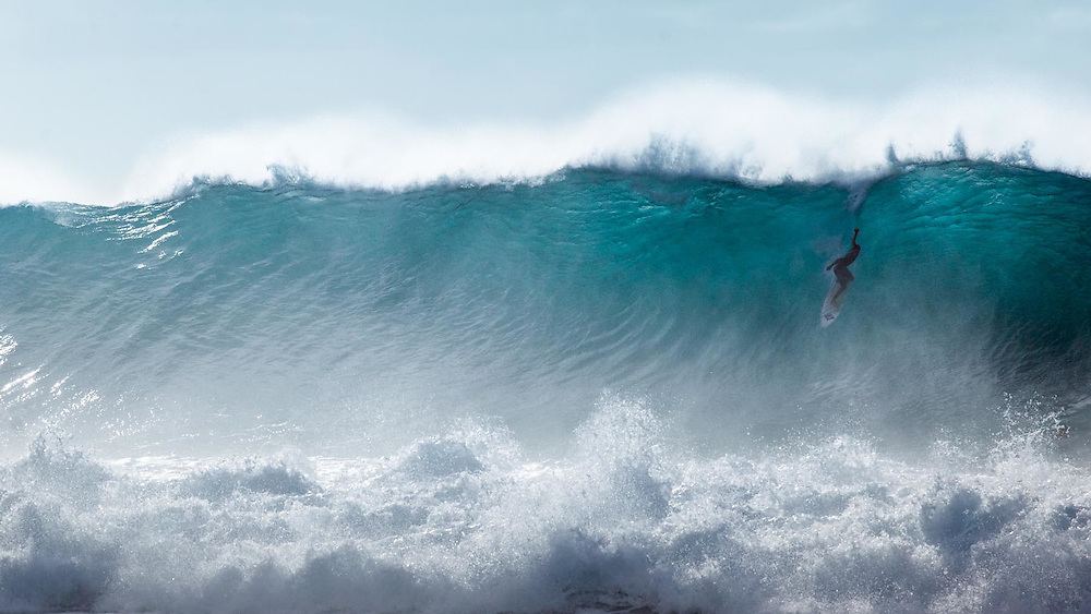 Surfers enjoy the last big swell of the season on the North Shore of Oahu, Hawaii.