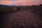 Sunrise at Sky Rock petroglyphs near Bishop in the Owens Valley area of California with the High Sierra in the background. These ancient writings are believed to be from the ancestors of what is currently the Owen's Valley Paiute Tribe.